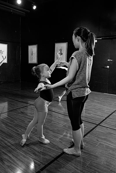 Dance Teacher helping young girl student with positioning at Fredericksburg Studio of the Arts